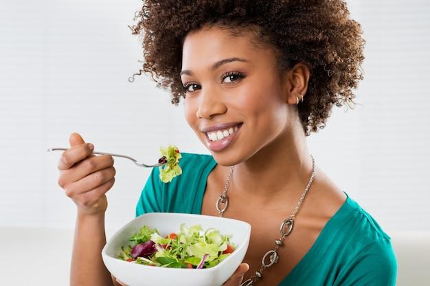 Афро-американская женщина ест салат