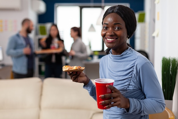 同僚の労働者と仕事の後に食べ物や飲み物を楽しんでいるアフリカ系アメリカ人の女性