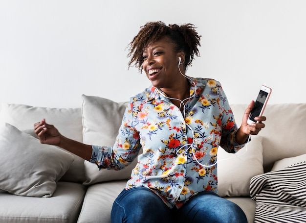 African american woman enjoying music at home leisure and music concept