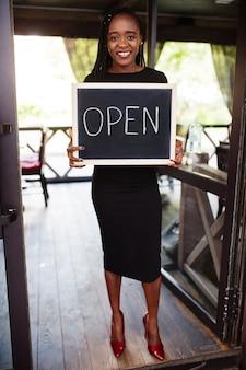 アフリカ系アメリカ人の女性は、サービス、レストラン、小売店、中小企業の所有者の準備ができているモダンなカフェのコーヒーショップでオープンウェルカムサインボードを保持しています。