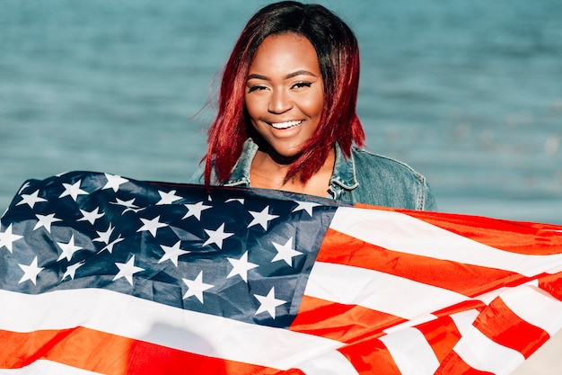 African american woman holding american flag