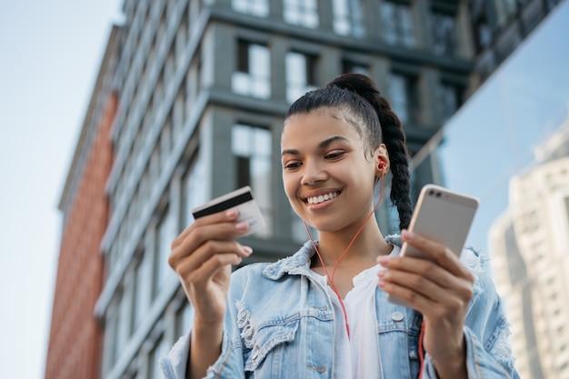 Афро-американская женщина, держащая кредитную карту, используя смартфон, делая покупки в интернете