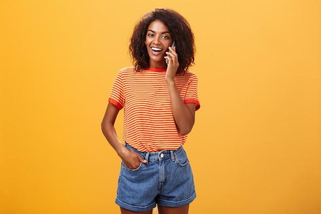 オレンジ色の壁の上の耳の近くにスマートフォンを保持しているアフリカ系アメリカ人の女性
