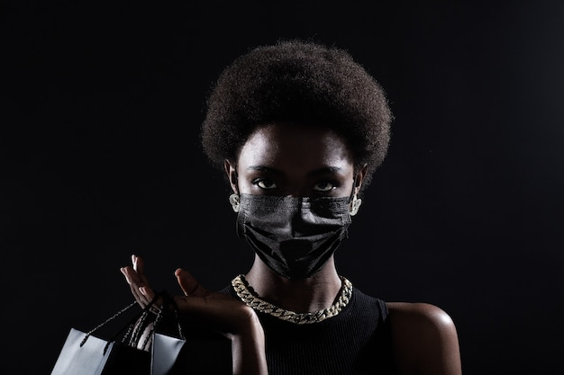 African american woman holds black shopping bags. sale and discounts on market and black friday concept.