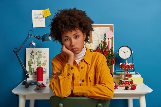 La donna afroamericana tiene la mano sotto il mento, guarda spiacevolmente la telecamera, posa contro un accogliente spazio di coworking