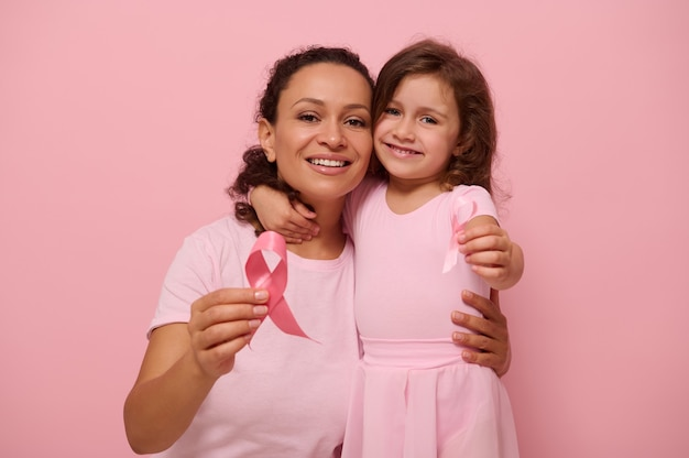 African american woman hugs her daughter, holding pink ribbon, cute smiles looking at camera, isolated on colored background with copy space. international day of fight against a breast cancer disease