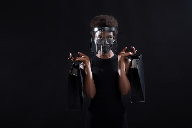 黒の医療用フェイスマスクと透明な保護フェイスシールドのアフリカ系アメリカ人女性は、ブラックフライデーのコンセプトで黒のショッピングバッグの安全性を保持しますcovidコロナウイルス保護