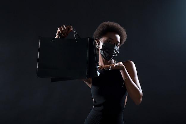 Афро-американская женщина в черной медицинской маске держит черные хозяйственные сумки. безопасность на концепции черной пятницы. защита от коронавируса covid-19.
