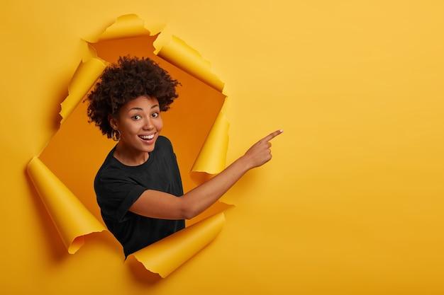 Афроамериканка в черной футболке, стоит в отверстии для бумаги, указывает на пустое пространство, стоит в разорванной бумаге
