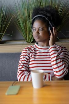 팟캐스트나 음악을 듣는 헤드폰을 끼고 있는 아프리카계 미국인 여성