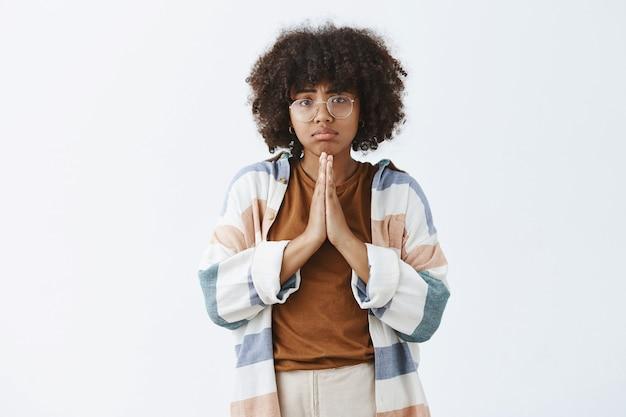Афроамериканка в беде, мрачная и расстроенная, держась за руки в молитве, хмурясь и дуясь, прося об одолжении или моля о помощи