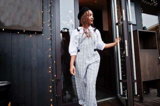 オーバーオールとクリスマスの装飾が施された屋外テラスのドアを出て歩くベレー帽のアフリカ系アメリカ人の女性。