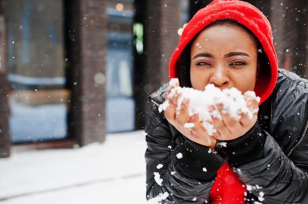 赤いパーカーを着たアフリカ系アメリカ人の女性は冬の日を楽しんでいます。