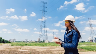 African American woman in safety helmet taking notes near high voltage line