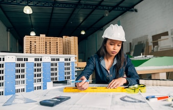 African-American woman in safety helmet working near model of building