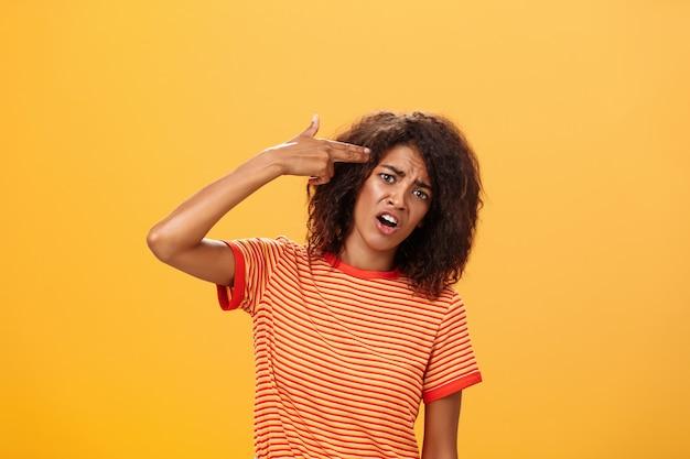 ストライプのtシャツを着たアフリカ系アメリカ人の女性が頭を傾けて額に指銃を置き自殺