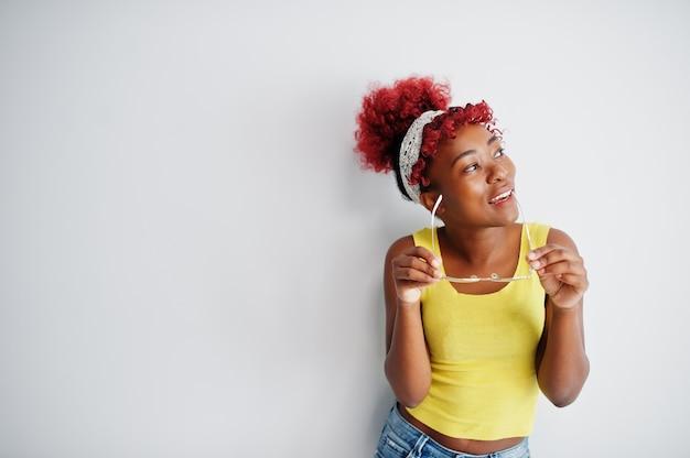 白い壁に黄色の一重項とeyglassesのアフリカ系アメリカ人の女性。