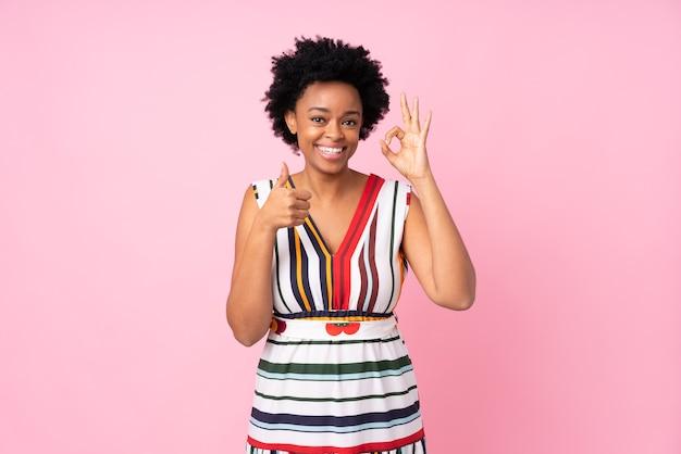 アフリカ系アメリカ人の女性がokサインと親指を立てるジェスチャーを示して孤立