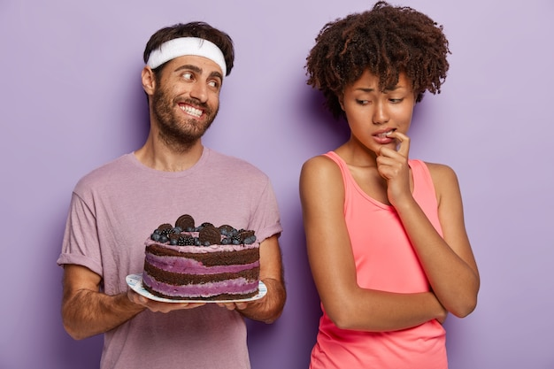 La donna afroamericana tiene il dito sulla bocca, prova la tentazione mentre guarda la deliziosa torta ai mirtilli