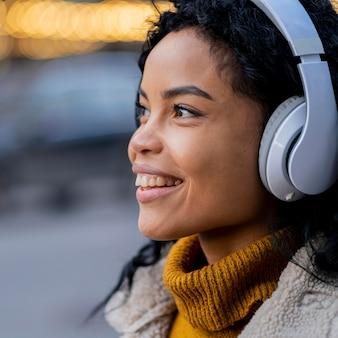 屋外で音楽を聴いているアフリカ系アメリカ人の女性