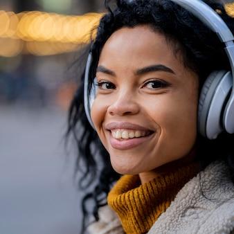 外で音楽を聴いているアフリカ系アメリカ人の女性