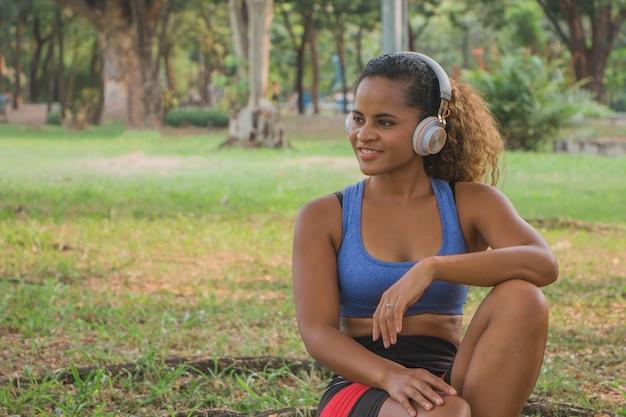 ヘッドフォンで音楽を聴き、公園で笑っているアフリカ系アメリカ人の女性。