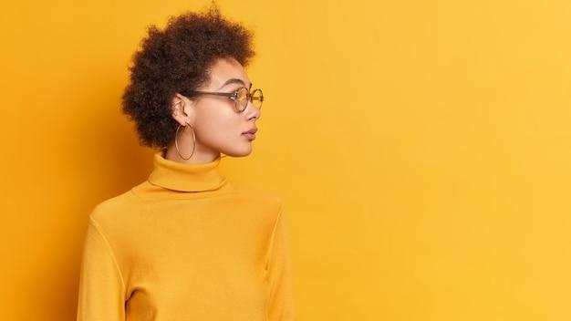 아프리카 계 미국인 여성은 사려 깊은 표정으로 옆으로 쳐다 보며 머리를 옆으로 집중하여 거리에 집중하고 투명 안경 터틀넥을 착용합니다.