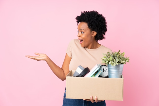 African american woman making a move while picking up a box full of things