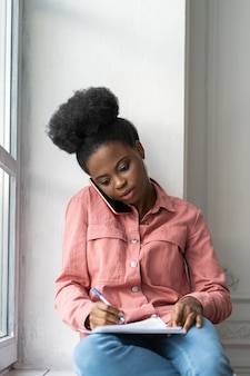 African american woman making notes clarifies information talking on phone sitting on windowsill