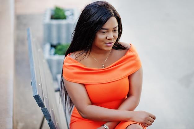 African american woman model xxl in orange dress.