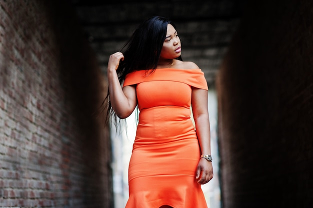African american woman model xxl in orange dress.