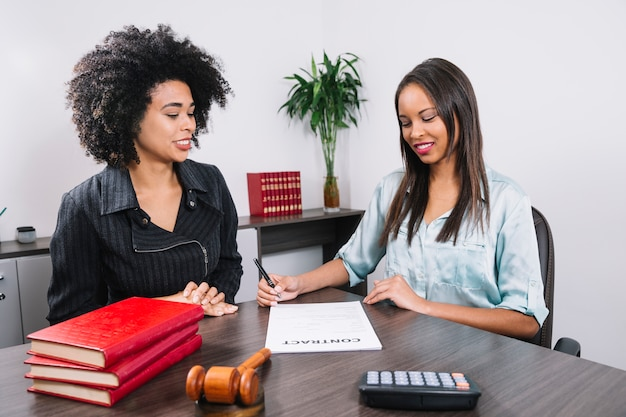 African american woman near lady writing in document at table