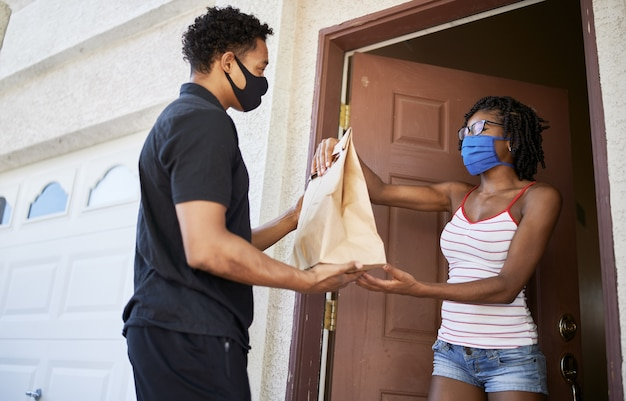 마스크를 착용하는 동안 주문을 받기 위해 문을 여는 아프리카 계 미국인 여자