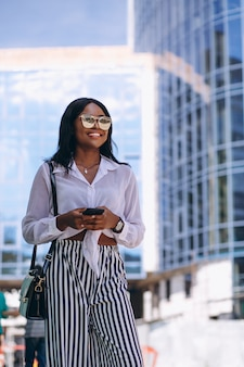 African american woman outdoors by the skyscraper with phone