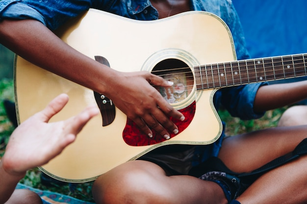 African american woman playing on a guitar