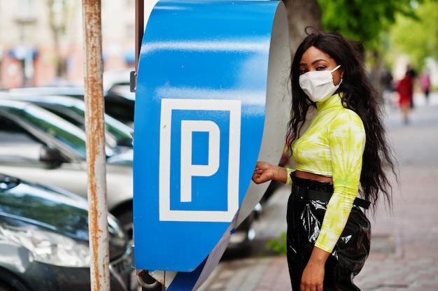 アフリカ系アメリカ人の女性が駐車場の有料ステーションターミナルを使用して、バクテリア、ウイルス、伝染病からの感染から保護するために顔のマスクでポーズをとっています。