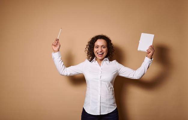 鉛筆と日記を手に持って手を上げ、歯を見せる笑顔で笑い、カメラを見て、コピースペースのあるベージュの壁に立っているアフリカ系アメリカ人の女性