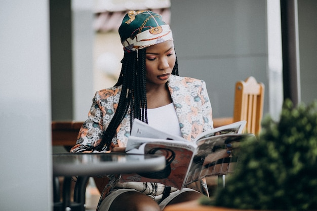 African american woman reading magazine in a cafe