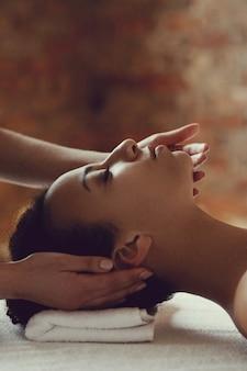 Афро-американская женщина получает расслабляющий массаж в спа-салоне