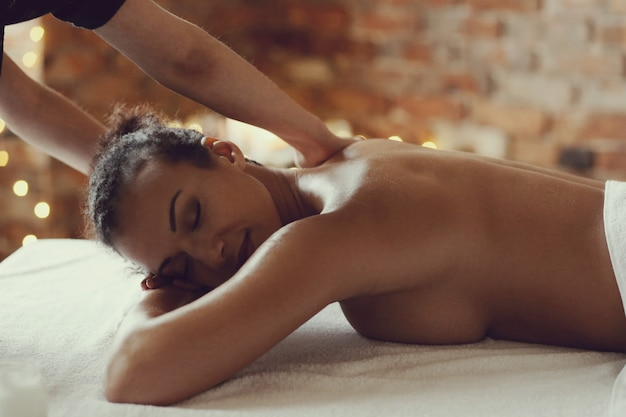 African american woman receiving a relaxing massage at the spa