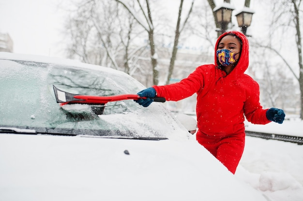 African american woman in red hoodie and face mask clean car from snow in winter day.