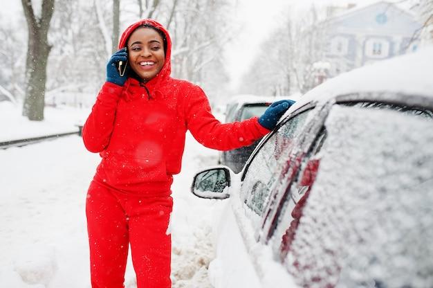 African american woman in red hoodie speak by phone near car in winter day.