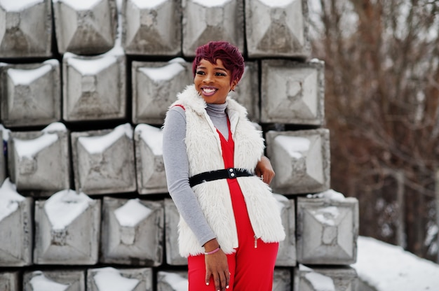 African american woman in red pants and white fur coat jacket posed at winter day against snowy stone background.