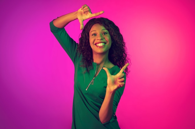 African-american woman's portrait on pink background in neon