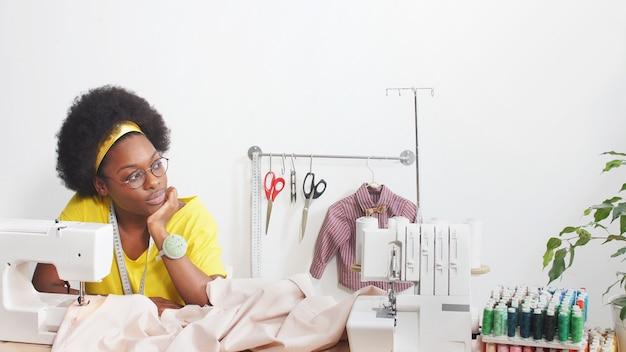 African-american woman sews clothes in her favorite studio, workshop