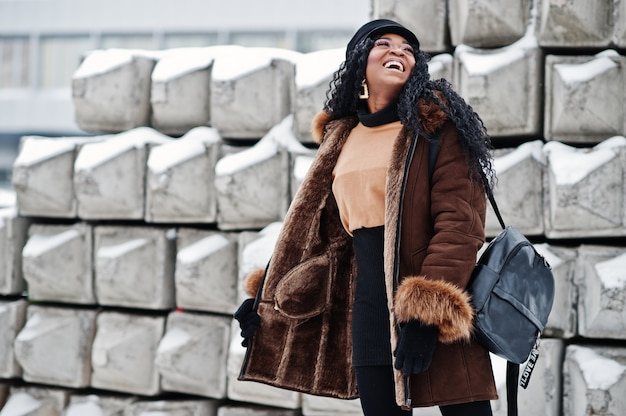 African american woman in sheepskin coat and cap posed at winter day against snowy stone background.