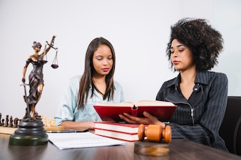 African American woman showing book to lady at table with document, statue and chess