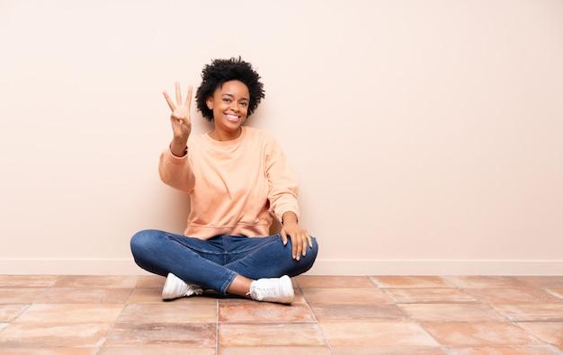 床に座っているアフリカ系アメリカ人の女性