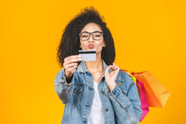 アフリカ系アメリカ人の女性の笑顔とカラフルなショッピングバッグとクレジットカードでうれしそうな