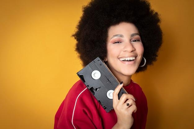 アフリカ系アメリカ人の女性、笑顔、カジュアルな服を着て、レトロなビデオテープを持っています